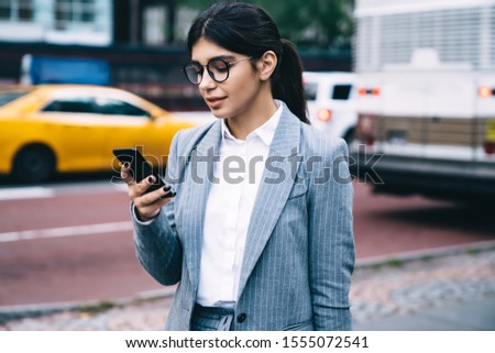 Confident entrepreneur dressed in formal wear typing sms message on smartphone standing at city urban area, female proud ceo in stylish glasses installing app on modern cellphone using 4G internet