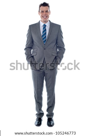 Confident executive posing with hands in pocket. Smiling at camera