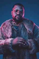 Confident fashion black man with fur coat and glasses
