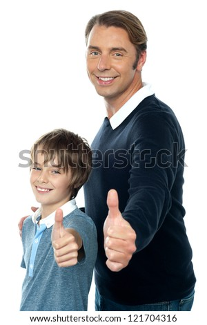 Confident father and son duo  gesturing thumbs up sign. Smiling faces