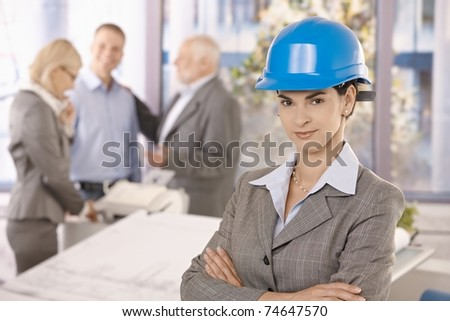 Confident female architect wearing hardhat in office, smiling at camera with arms folded, coworkers working in background.?