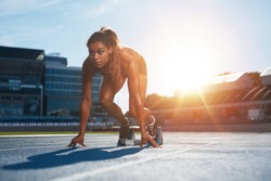 Confident female athlete in starting position ready for running. Young woman about to start a sprint looking away with bright sunlight from behind.