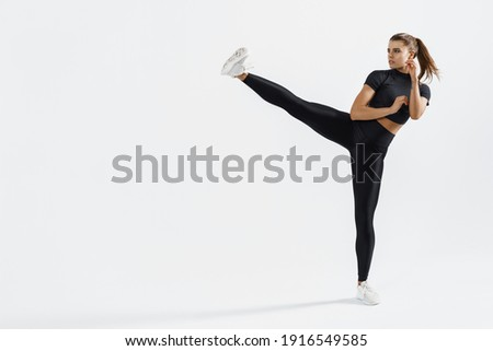 Confident female athlete workout, practice leg kicks, kicking air in sportswear. Muscular trained woman kicking with raised feet, exercise kickboxing moves, white background.