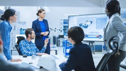 Confident Female Automotive Engineer Reports to Diverse Team of Specialists, Managers, Businesspeople and Investors Sitting at the Conference Table, She Shows TV with 3D Prototype of Electric Car