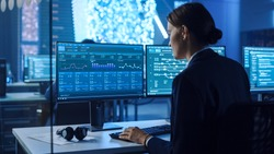 Confident Female Data Scientist Works on Personal Computer in Big Infrastructure Control and Monitoring Room with Neural Network. Woman Engineer in an Office Room with Colleagues.