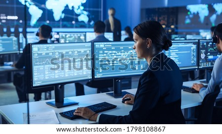 Confident Female Data Scientist Works on Personal Computer Wearing a Headset in Big Infrastructure Control and Monitoring Room. Woman Engineer in a Call Center Office Room with Colleagues. Photo stock ©