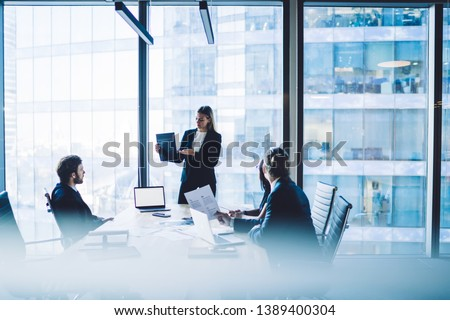 Confident female director dressed in formal suit making presentation of productive strategy near desktop with laptop computer with blank screen area for advertising text or financial website #1389400304