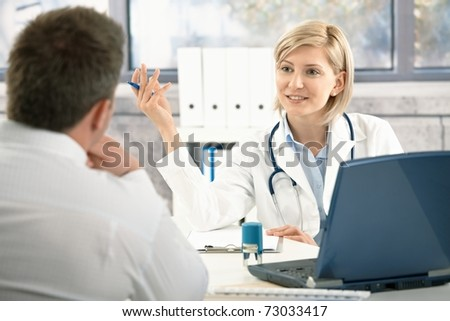 Confident female doctor discussing diagnosis with patient in office, smiling.?