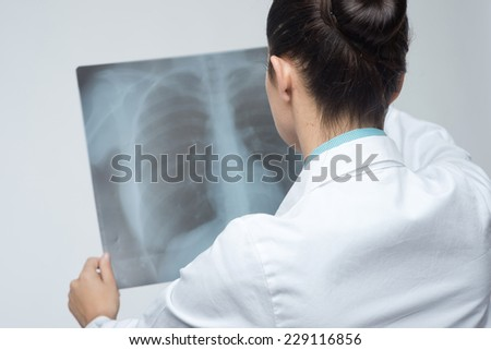 Confident female doctor examining accurately a rib cage x-ray.