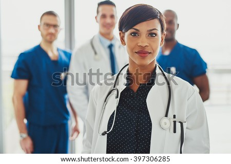 Confident female doctor in front of team, looking at camera smiling, multiracial team with black female doctor