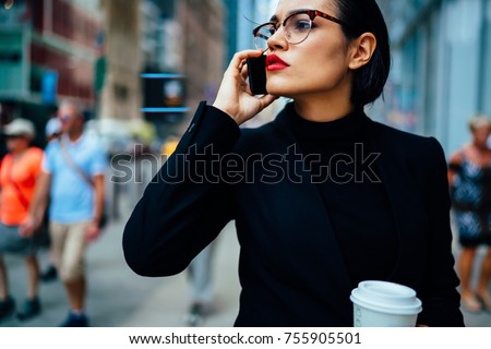 Confident female executive manager with trendy red lips talking on phone about work strolling with coffee to go, serious business woman in black elegant formal wear having mobile conversation outdoors