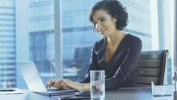 Confident Female Executive Works on a Laptop Sitting at Her Desk in Modern Office with Big City View. Smiling Successful Busiesswoman Uses Laptop.