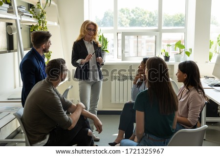 Confident female leader, coach holding briefing for multiracial team employees in office, explaining business strategy, plan to subordinates. Businesswoman at company meeting with diverse colleagues.