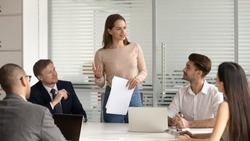 Confident female manager presenting financial report speak at team meeting talk to employees group, business woman company executive leader hold papers explain new business plan at corporate briefing