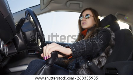 Confident female racer drives car. Young woman drives car, focus on her hand switching transmission grip Biker dress black leather jacket, sunglasses, bright sunbeams on right corner