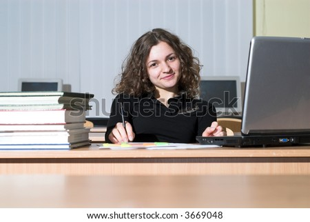 Confident female student is waiting for something and playing with her pen.
