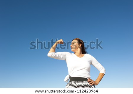 Confident focused and physical strong mature woman showing off her biceps, isolated with blue sky as background and copy space.
