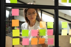 Confident focused businesswoman wearing glasses writing ideas or tasks on sticky papers on glass wall, female team leader, executive manager holding computer tablet, planning project, organize work
