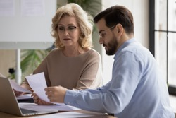 Confident focused middle aged 50s businesswoman in eyeglasses discussing marketing research results or company sales statistics paper reports with skilled young male employee at office meeting.