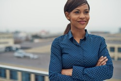 Confident friendly black business woman standing with folded arms on the rooftop of an urban commercial building smiling as she looks to the side of the camera