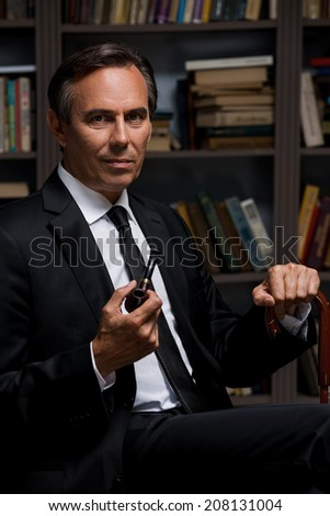 Confident gentleman. Confident mature man in formalwear holding pipe and cane while sitting against bookshelf