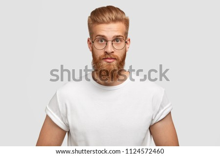 Confident ginger male with trendy hairstyle, wears spectacles, looks directly at camera, concentrated on something, dressed in casual white t shirt, poses against white background. Studio shot #1124572460
