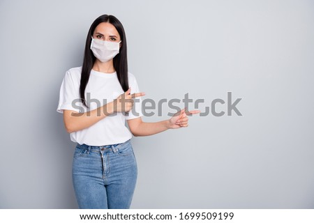Confident girl promoter in medical mask point index finger copyspace demonstrate coronavirus information present safety protection wear white t-shirt jeans isolated gray color background