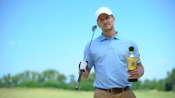 Confident golf player with gold cup and club smiling on camera, sport champion