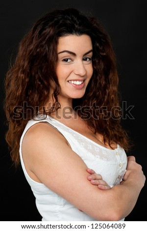 Confident gorgeous female model with perm long hair, standing sideways.