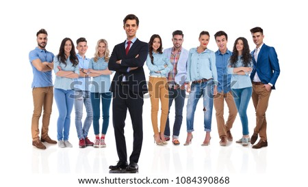 confident group leader standing on white background with hands folded while his casual team is behind him, full body picture #1084390868