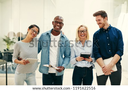 Confident group of diverse young businesspeople smiling and laughing together while standing side by side in a bright modern office #1191622516