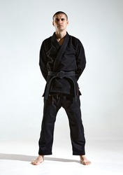 Confident guy in black kimono fighter posing in karate stance on studio background with copy space