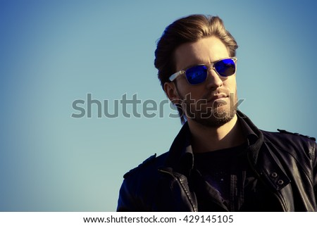 Confident handsome man in sunglasses and leather jacket over blue sky. Men\'s beauty, fashion. Outdoor portrait.