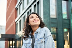 Confident happy beautiful young hipster African American woman wearing denim jacket looking up standing on city street outdoors dreaming, thinking or good future on urban buildings background.