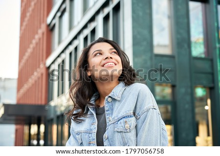 Confident happy beautiful young hipster African American woman wearing denim jacket looking up standing on city street outdoors dreaming, thinking or good future on urban buildings background. ストックフォト ©
