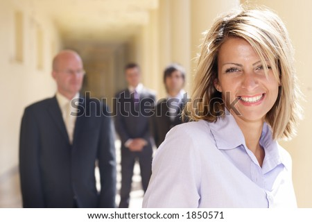 confident happy  businesswoman with her team behind her - stock photo