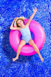 Confident happy little 5 year old girl in a swimming pool floating on a bright pink plastic tube in her swimsuit waving at the camera with a cheerful grin, conceptual image on blue painted water.