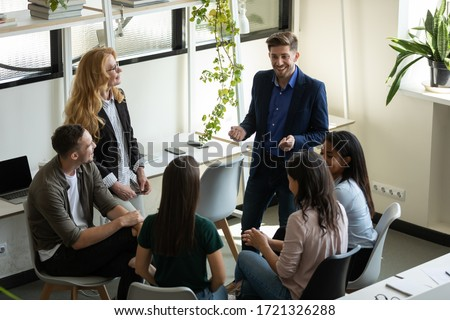 Confident happy male leader, coach holding briefing for team employees in office, explaining business strategy, plan to subordinates. Smiling businessman at company meeting with diverse colleagues.