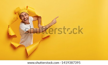 Confident happy man in casual white t shirt, points at upper right corner, invites going in this direction, demonstrates welcoming gesture, stands in torn paper hole, says you must see product Stock foto ©