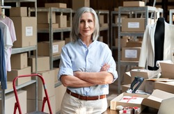 Confident happy mature older 60s woman retail seller, entrepreneur, clothing store small business owner, supervisor looking at camera standing arms crossed in delivery shipping warehouse, portrait.
