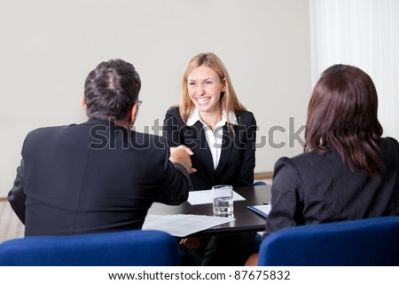 Confident happy young female candidate shaking hands during a job interview at the office with managers