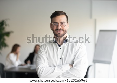 Confident happy young male manager in eyeglasses standing with folded hands head shot portrait. Smiling company owner, startup businessman, team leader, successful employee looking at camera.
