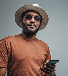 Confident hindu with mobilephone looks at camera posing in studio