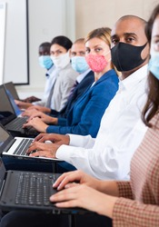 Confident hispanic businessman in protective mask sitting with laptop in row with colleagues during business training. Precautions during mass events in coronavirus pandemic concept