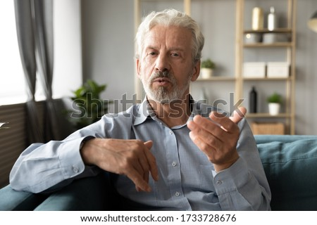 Confident hoary middle aged handsome man looking at camera, holding business talk with clients partners online. Web camera view mature senior grandfather chatting with friends family via video call.