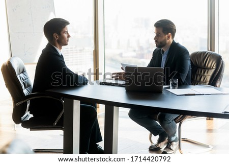 Confident hr manager talking to candidate on job interview, asking questions about cv, sitting at desk in modern office with panoramic windows, colleagues, business partners discussing project