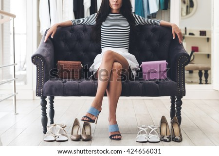 Confident in her choice. Part of beautiful young woman keeping legs crossed at knee while sitting on sofa at the shoe store #424656031