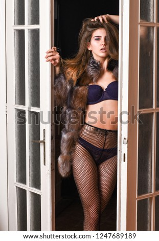 Confident in her magnetism. Seduction art concept. Woman seductive wear luxury fur and lingerie. Female lover enter bedroom doors. Fashion lady confident and seductive. Woman seductive appearance.