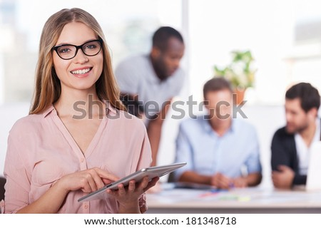 Confident in her team. Confident young woman in glasses working on digital tablet and smiling while three people working on background