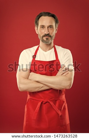 Confident in his culinary craft. Cook with beard and mustache wearing apron red background. Man mature cook posing cooking apron. Chief cook and professional culinary. Cook food at home. Fine recipe.